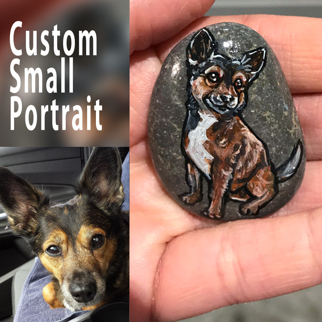 a small stone, custom painted with a pet portrait of a black and brown dog.
