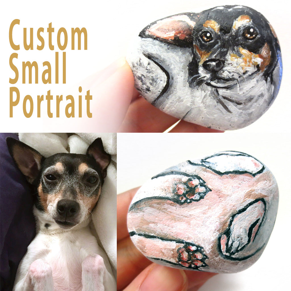 a beach stone hand painted with a portrait of a terrier dog