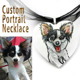 a personalized dog portrait of a black and white papillon, painted on a heart shaped wood pendant and handmade into a necklace