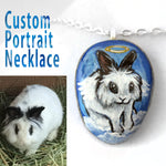 a custom art necklace, with a portrait of a white and black lionhead rabbit as an angel, painted on a beach stone