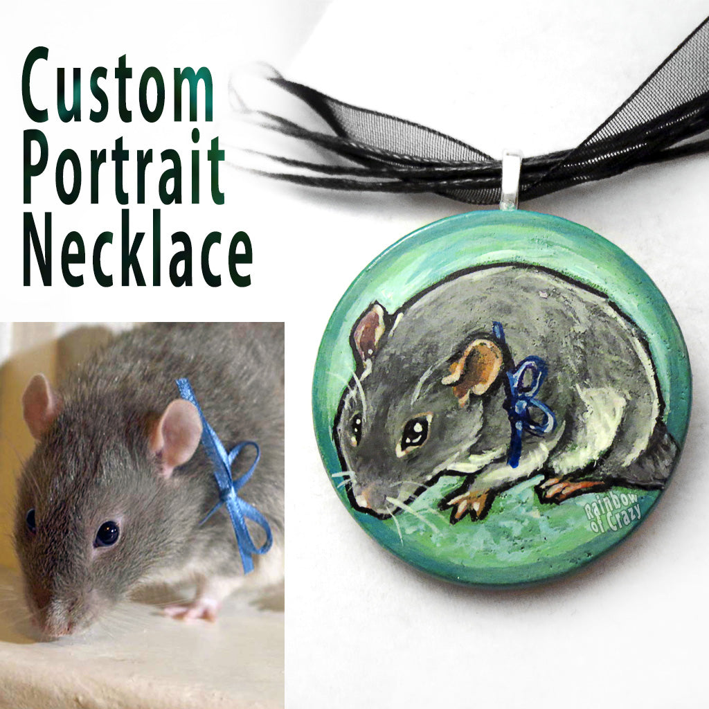 A custom pet portrait painting, on a circle wood necklace, of a grey mouse wearing a blue ribbon