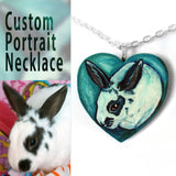 A personalized pet portrait necklace, with art of a white and black bunny rabbit, painted on a heart shaped wood pendant