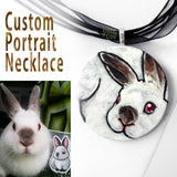 A custom pet portrait painting, on a circle wood necklace, of a brown and white bunny rabbit with red eyes.