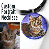 A custom pet portrait painting, on a circle wood necklace, of a brown and orange tabby cat with yellow eyes