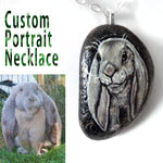 A portrait necklace, handmade with a small beach rock, custom painted with a portrait of a grey bunmy rabbit