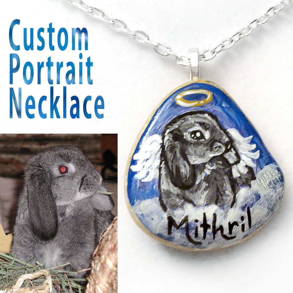 A custom pet portrait painting of a grey mini lop bunny rabbit, painted as an angel, on a small beach rock, crafted into a pendant necklace.