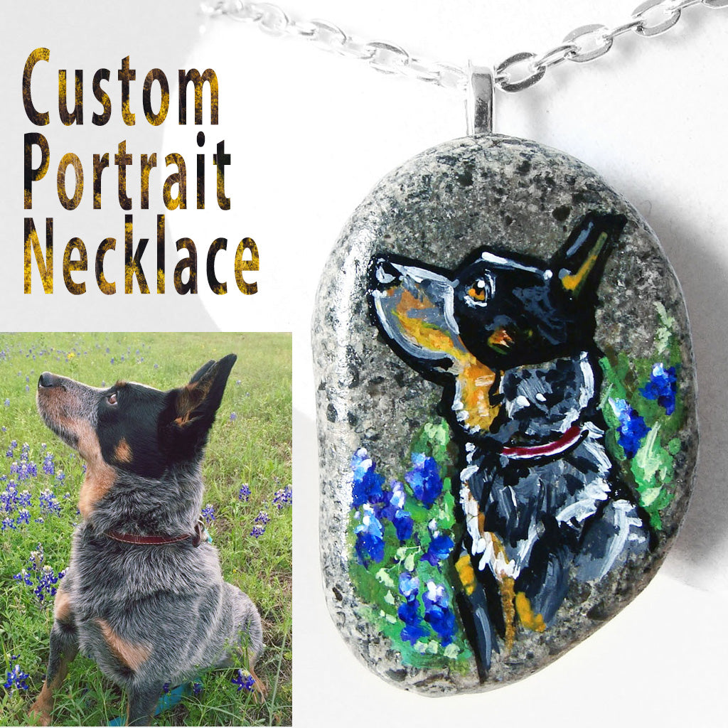 A custom pet portrait necklace, painted on a beach stone, of an Australian Cattle Dog, sitting in a field of flowers.