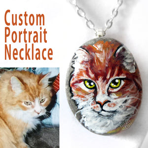 A small beach rock, custom painted with a portrait of an orange cat and crafted into a pendant necklace.