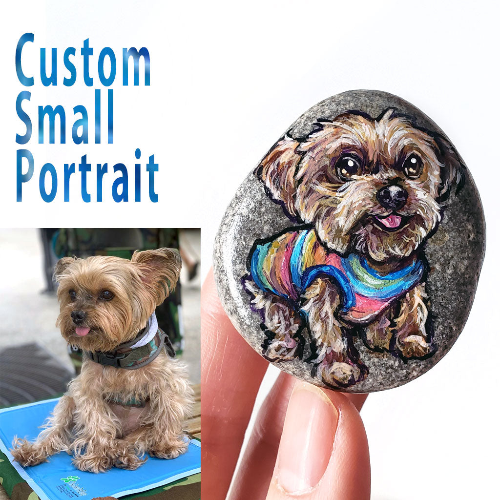A small beach stone hand painted with the portrait of a yorkshire terrier dog wearing a rainbow shirt