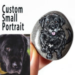 a small beach pebble painted with art of a black dog