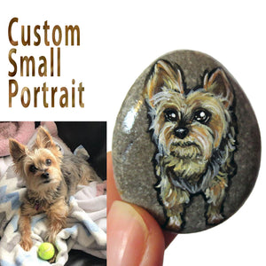 a small beach pebble with custom art of a yorkshire terrier dog