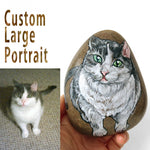 A large beach stone, hand painted with a custom portrait of a grey and white cat with green eyes