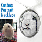 A personalized pretty portrait necklace on a small beach rock, with a painting of a white rabbit.