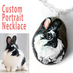 a personalized pet portrait of a black and white lionhead bunny rabbit, painted on a beach rock and handmade into a pendant necklace
