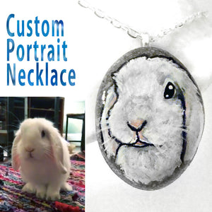 a custom pet portrait necklace of a white bunny rabbit, painted on a small beach rock