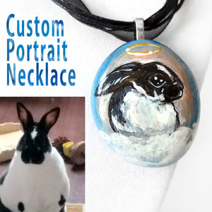 a custom portrait necklace of a black and white rabbit painted as an angel, on a small beach rock