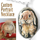 A pendant necklace handmade from a small beach rock, painted with a portrait of a brown mini lop rabbit.