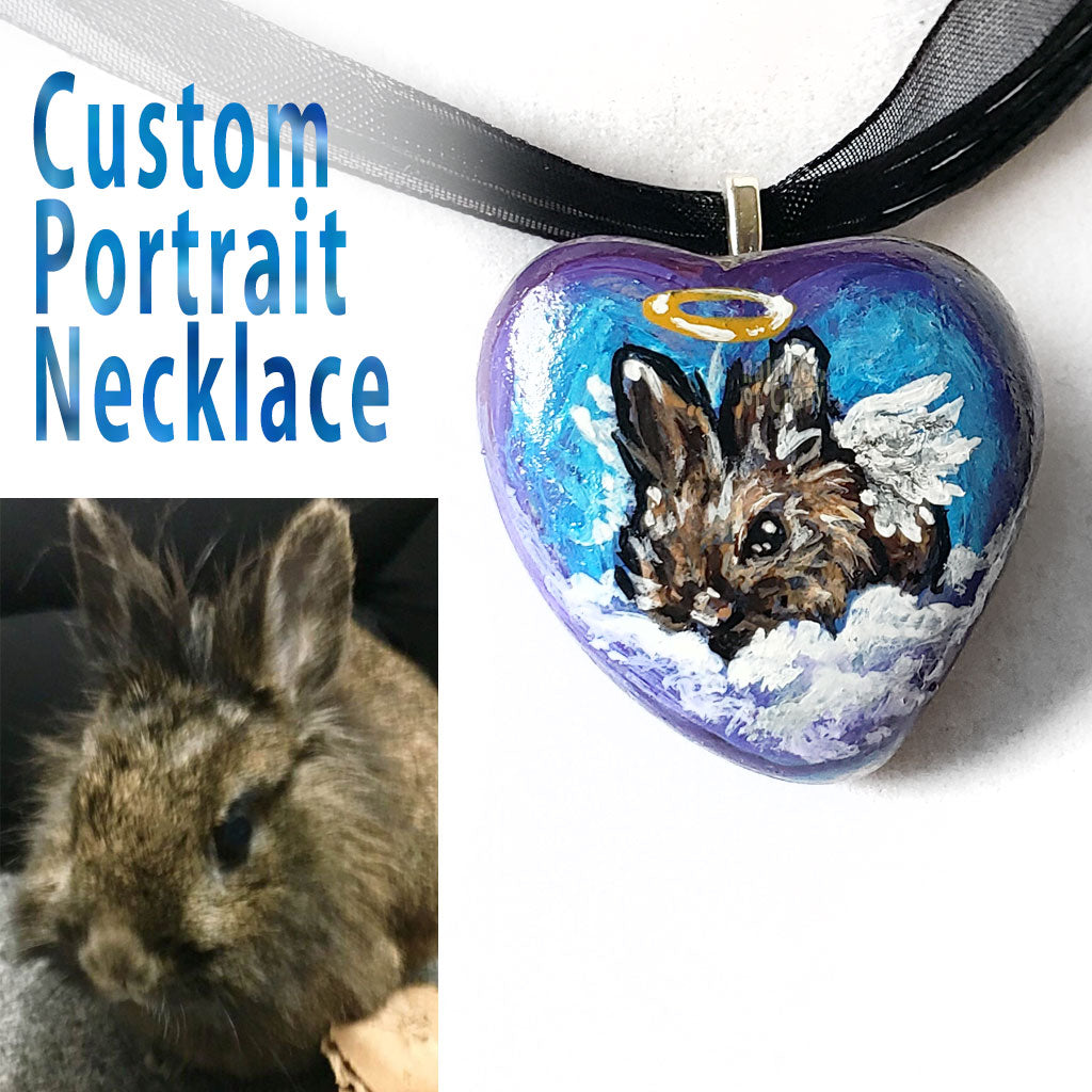 A pendant necklace created from a small beach stone, painted with a portrait of a brown lionhead rabbit as an angel.