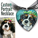 A custom dog portrait necklace, painted on a wood heart, with a King Charles Spaniel with flowers on its head.
