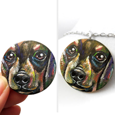 A round wood pendant is hand painted with a portrait of a dacshund dog, and is available as either a keepsake or a pendant necklace
