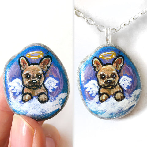 a small beach stone painted with dog art: a french bulldog as an angel in the clouds. available as a stone keepsake or a pendant necklace