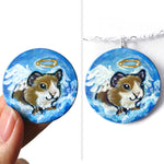 a wood circle disc, with pet art: a painting of a brown and white guinea pig as an angel, on clouds in a blue sky. available as a keepsake or pendant necklace