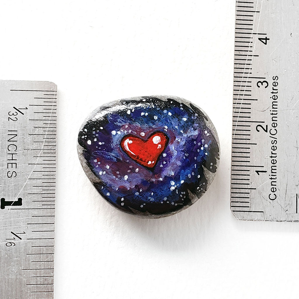 "a beach stone, painted with a heart in a starry galaxy sky, next to two rulers to show its size. it measures 1 3/16"" x 1 1/16"" or 3 cm x 2.7 cm"