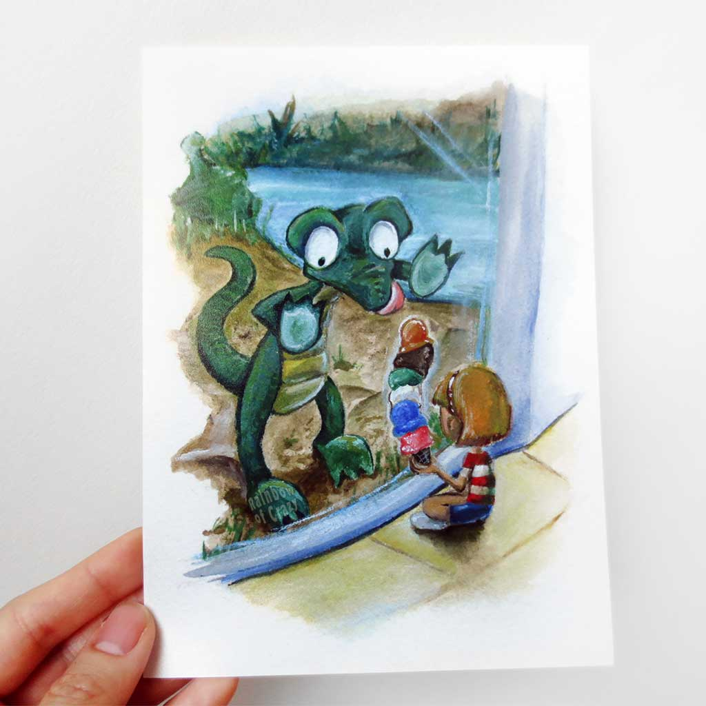 A hand holds up a 5x7 art print of an illustration: a crocodile up against the glass at the zoo, staring at the ice cream that a little girl is holding.