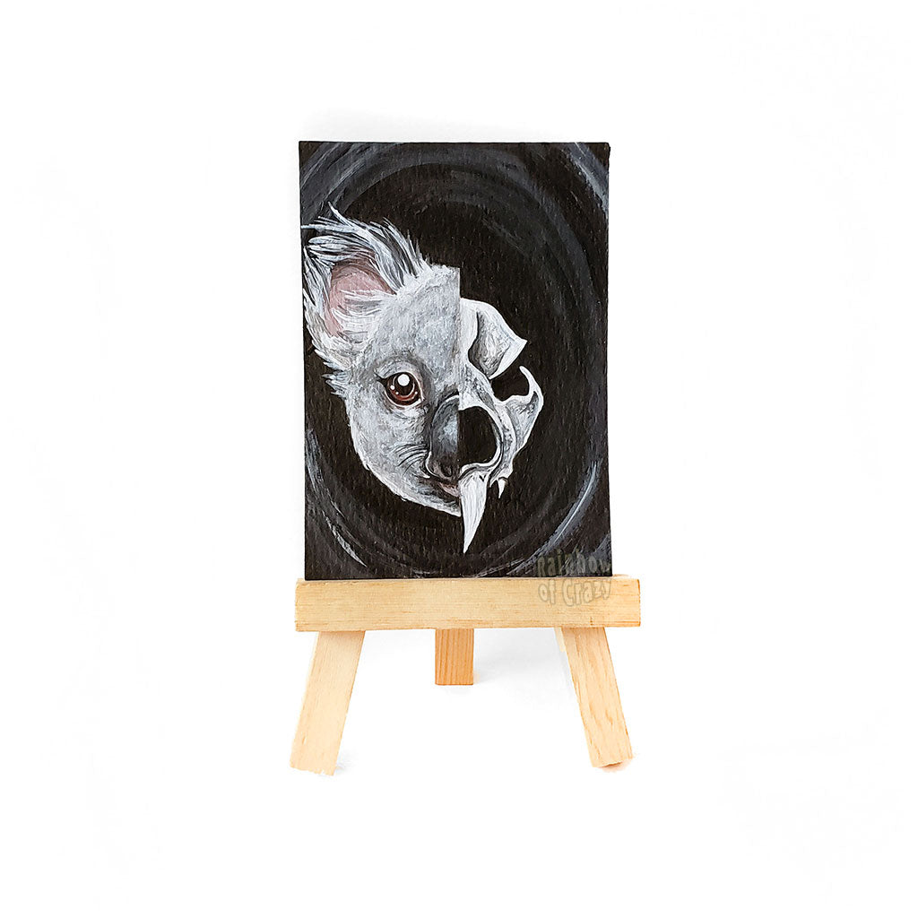 a small easel with a miniature painting that is ACEO sized (2.5 inches by 3.5 inches), of a split portrait: the left side is painted with a koala, and the right side is painted with a stylized koala skull.