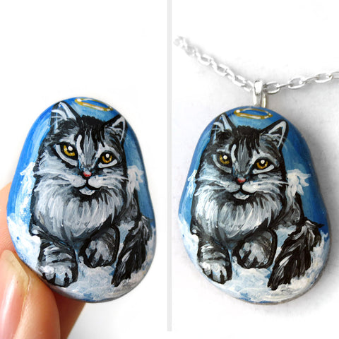 A beach stone painted with a cat portrait of a grey maine coon cat as an angel in the clouds, available as either a keepsake or a pendant necklace.
