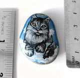 "A beach rock hand painted with a maine coon cat as an angel in the clouds, next to two rulers for sizing. It measures 1 1/2"" x 1 3/16"" or 3.8 cm x 3 cm"
