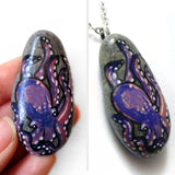 An oval shaped beach stone has been hand painted with a purple and pink octopus and is available as either a keepsake or a pendant necklace