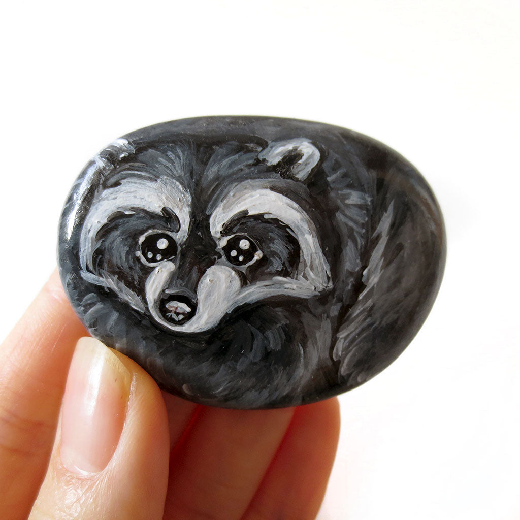 A small beach rock painted with raccoon art