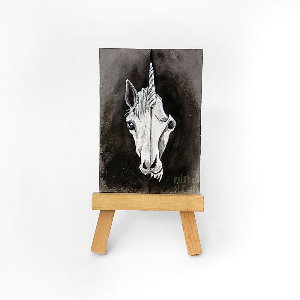 an easel with an ACEO sized miniature painting (2.5 inches by 3.5 inches) of a split image: the left side is a white unicron and the right side is a unicorn skull with sharp fangs
