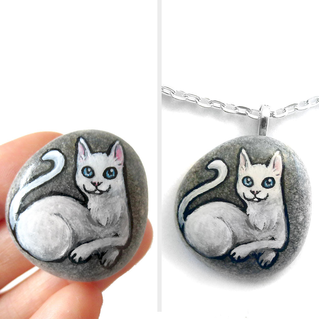 A small beach stone hand painted with a portrait of a white cat with blue eyes, available as a stone or pendant necklace.