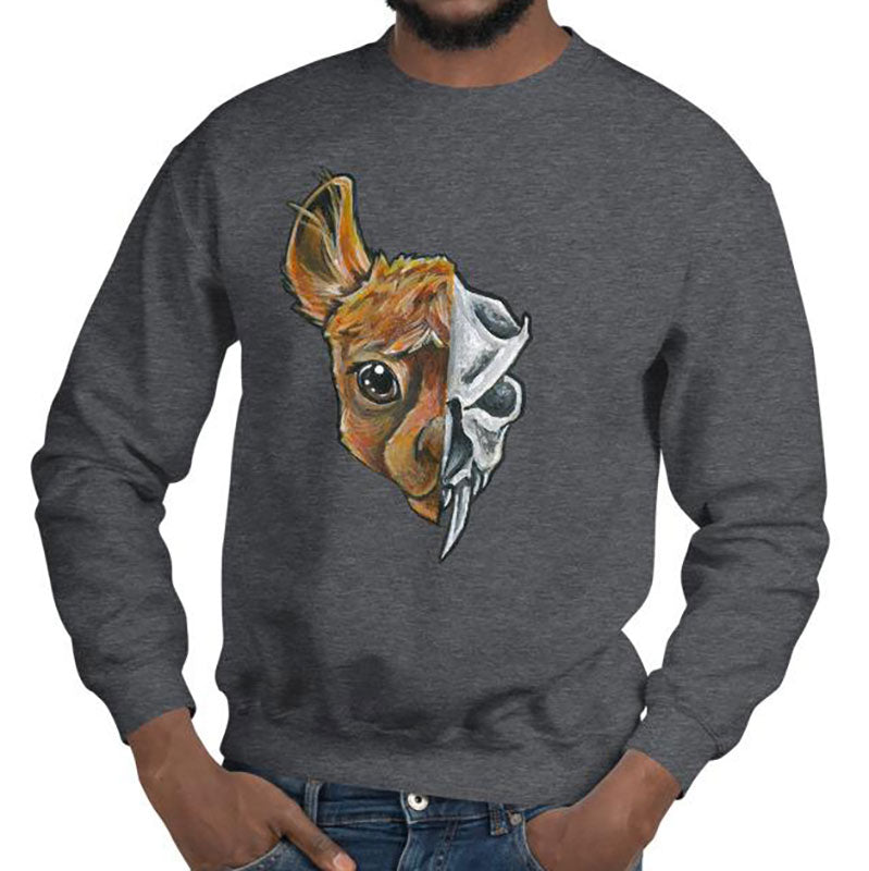 A man is wearing a unisex sweatshirt in the colour dark heather grey, printed with art split into two: the left side features the face of a brown alpaca, and the right side features an evil looking alpaca skull.
