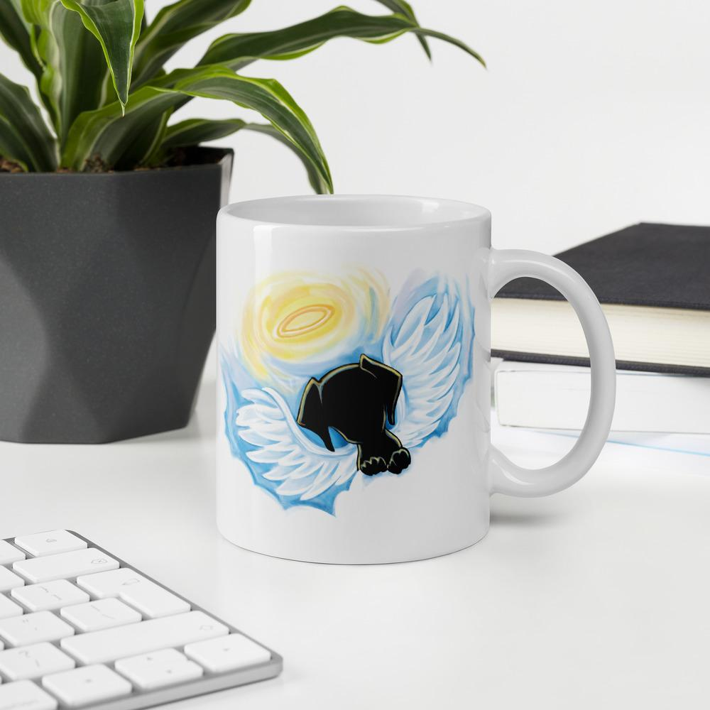 An 11 oz ceramic coffee mug is printed with art of a black dog as an angel with wings and halo, peeking out from the clouds