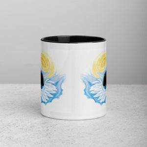An 11 oz ceramic coffee mug, with black trim, is printed with a graphic of a black dog as an angel with wings and halo, peeking out from the clouds
