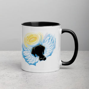 An 11 oz ceramic coffee mug, with black trim, is printed with an image of a black dog as an angel with wings and halo, peeking out from the clouds