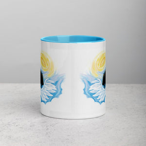 An 11 oz ceramic coffee mug, with blue trim, is printed with an illustration of a black dog as an angel with wings and halo, peeking out from the clouds