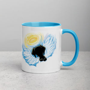 An 11 oz ceramic coffee mug, with blue trim, is printed with artwork of a black dog as an angel with wings and halo, peeking out from the clouds