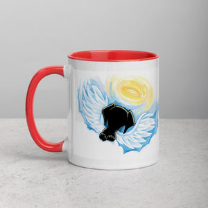 An 11 oz ceramic coffee mug, with red trim, is printed with art of a black dog as an angel with wings and halo, peeking out from the clouds