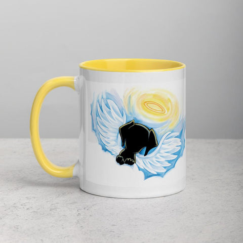 An 11 oz ceramic coffee mug, with yellow trim, is printed with a painting of a black dog as an angel with wings and halo, peeking out from the clouds