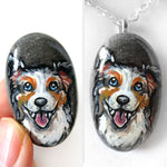 a small beach rock, hand painted with art of a smiling Australian Shepherd dog, available as a stone keepsake or pendant necklace.