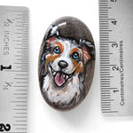 "A small rock, hand painted with art of a smiling Australian Shepherd, next to twonrulers to show its size: 1 9/16"" x 15/16"" or 4 cm x 2.4 cm"