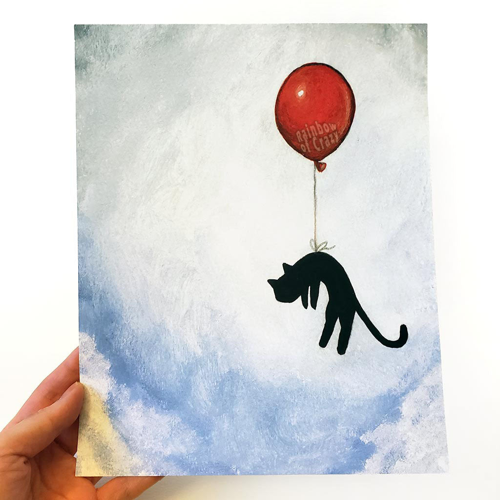 an art print with an illustration of a silhouette of a black cat, attached by the waiste to a big red balloon, as it floats through a blue cloudy sky