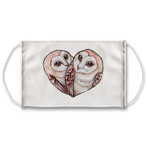 A white reuseable face mask is printed with an illustration of two barn owls together, forming the shape of a heart