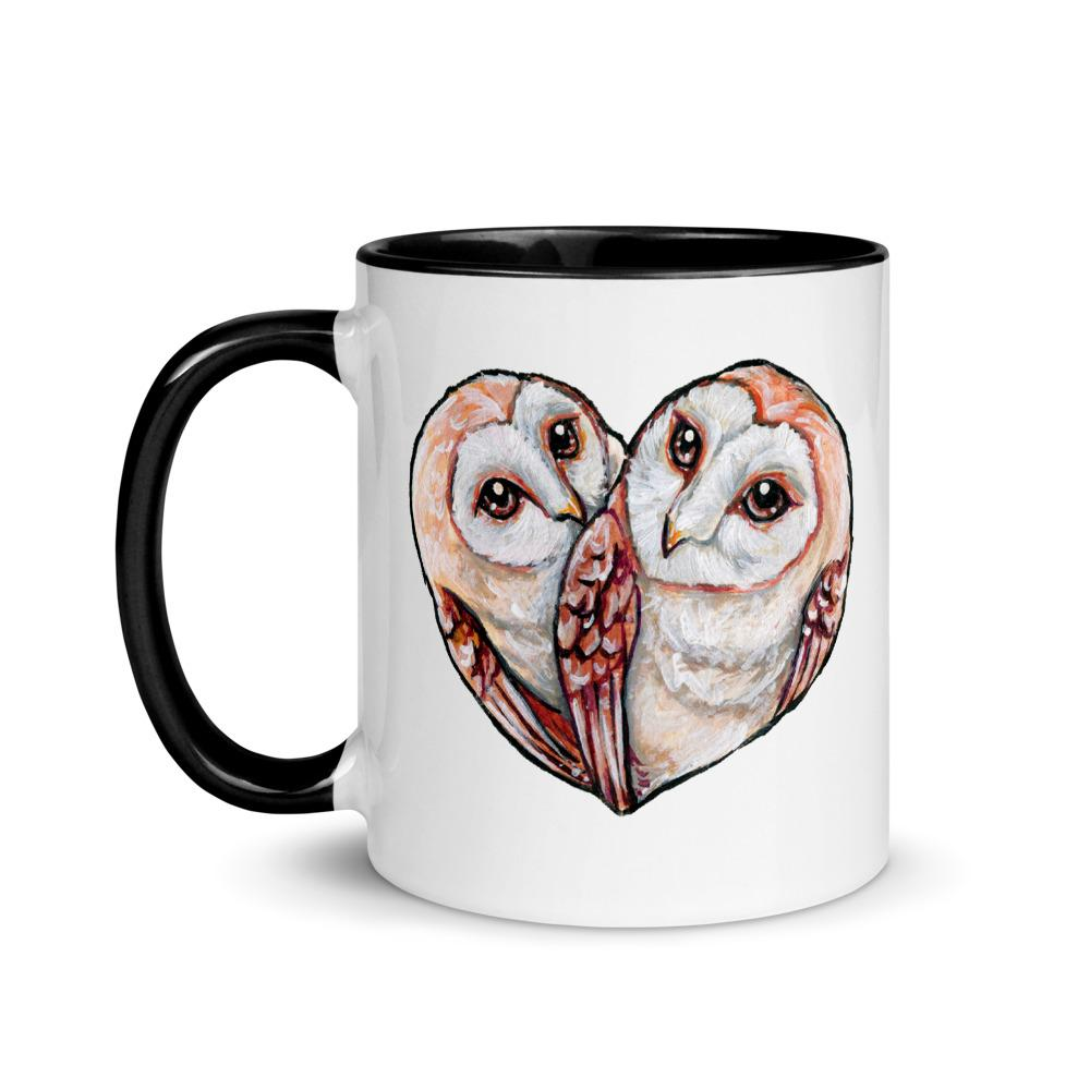 An 11 oz white ceramic mug with black trim, printed with two barn owls close together forming the shape of a heart.