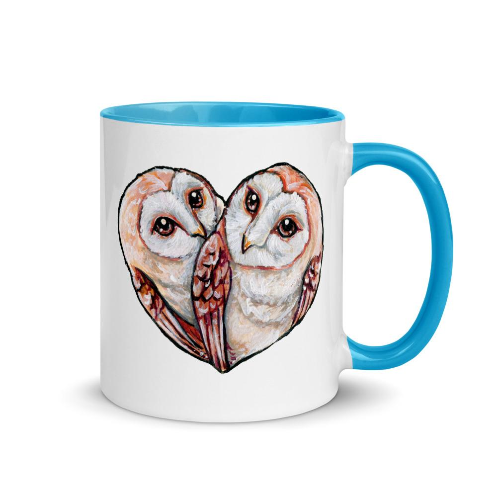 An 11 oz white ceramic mug with blue trim, printed with two barn owls close together forming the shape of a heart.