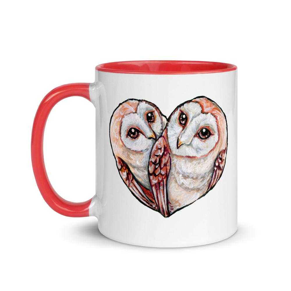 An 11 oz white ceramic mug with all red trim, printed with two barn owls close together forming the shape of a heart.